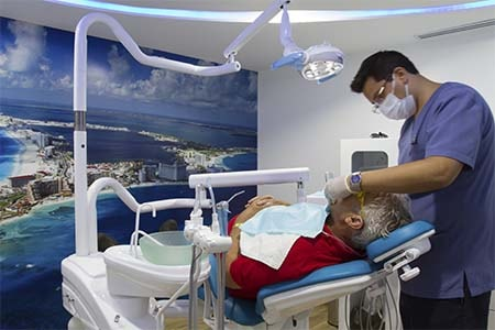 Dentist in Cancun checking an American patient.